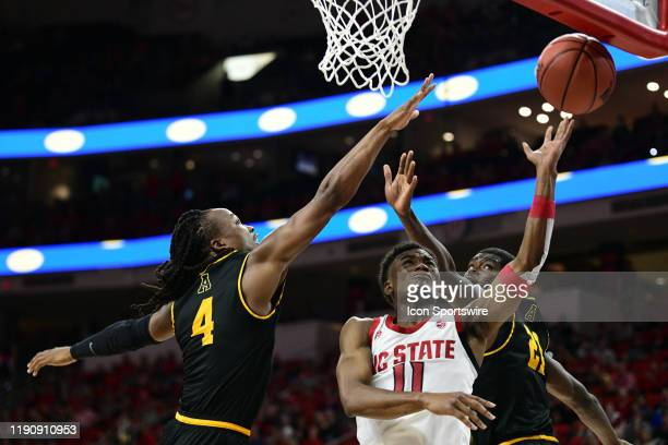 North Carolina State Wolfpack guard Markell Johnson shoots between Appalachian State Mountaineers guard O'Showen Williams and Appalachian State...