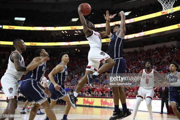 North Carolina State Wolfpack guard Markell Johnson soars through the air towards the basket as Duke Blue Devils center Vernon Carey Jr. Looks to...