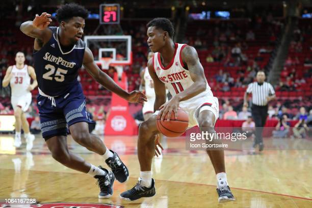 North Carolina State Wolfpack guard Markell Johnson with the ball while St Peter's Peacocks guard Cameron Jones tries to block him during the 1st...