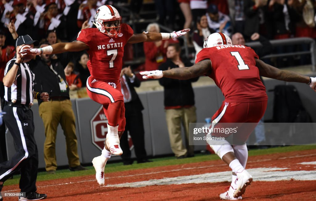 North Carolina State Wolfpack running back Nyheim Hines (7) celebrates with North Carolina State Wolfpack tight end Jaylen Samuels (1) after a touchdown run during the game between the North Carolina Tarheels and the NC State Wolfpack on November 25, 2017 at Carter-Finley Stadium in Raleigh, NC. NC State defeated North Carolina 33-21.