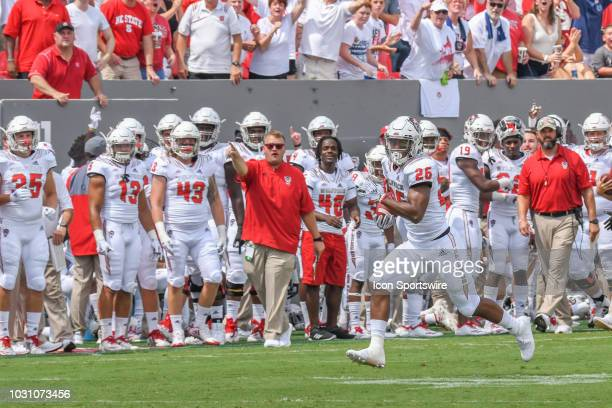 North Carolina State Wolfpack running back Trent Pennix runs to the end zone as North Carolina State Wolfpack bench cheers him on during the college...