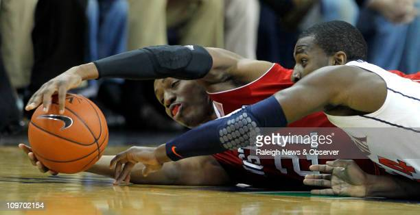 North Carolina State's CJ Williams left and Virginia's KT Harrell go after a loose ball during the first half at John Paul Jones Arena in...