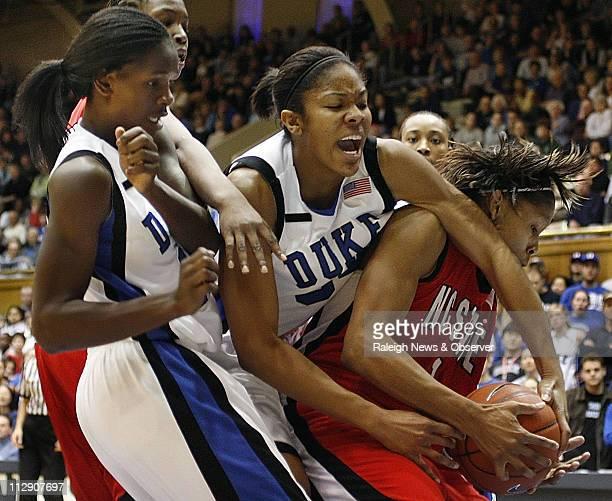 North Carolina State's Khadijah Whittington right wrestles a defensive rebound from Duke's Krystal Thomas as Bridgette Mitchell looks on during the...