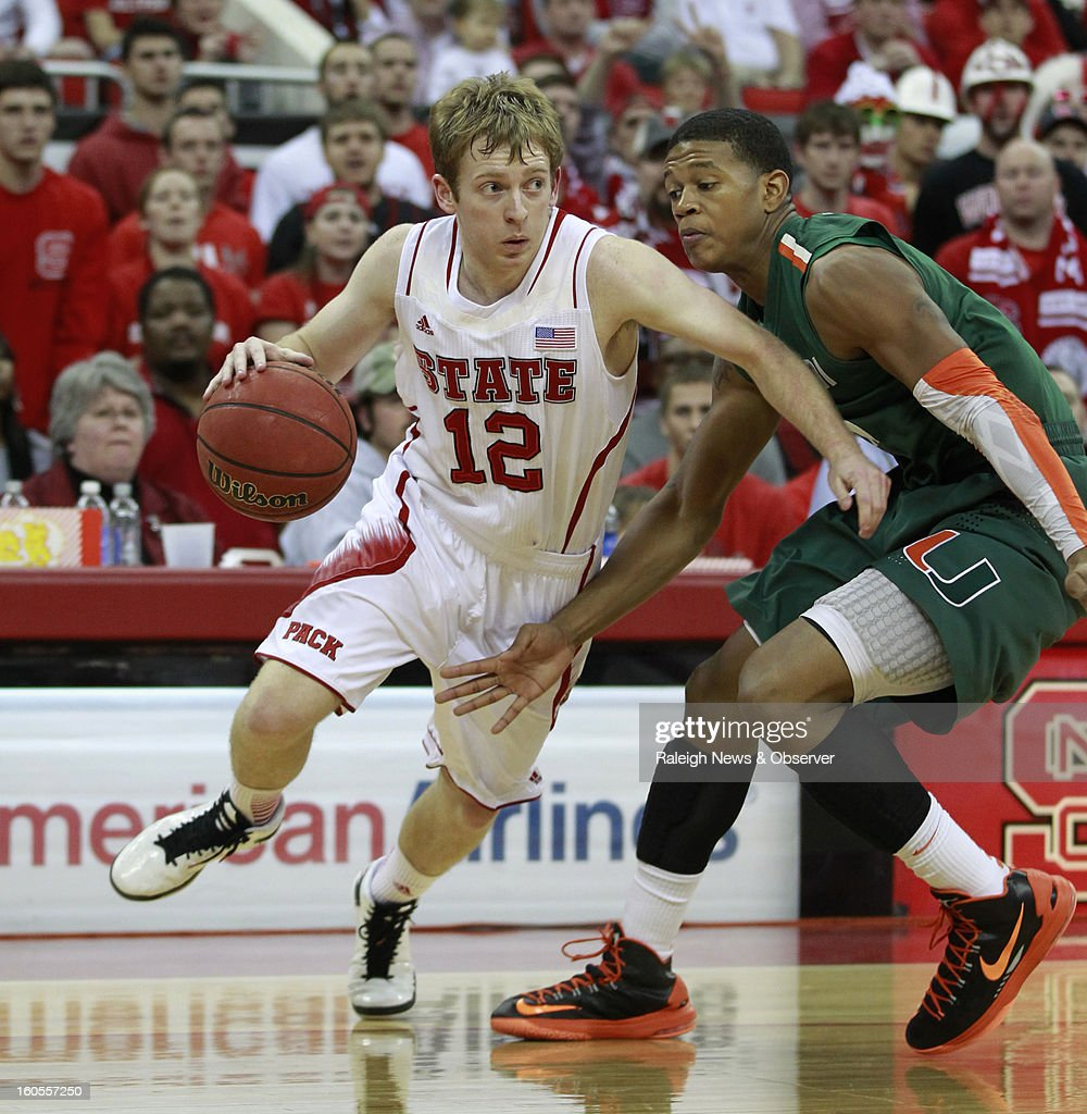 North Carolina State's Tyler Lewis (12) dribbles around Miami's Rion Brown during the second half of Miami's 79-78 victory at PNC Arena in Raleigh, North Carolina, on Saturday, February 2, 2013.