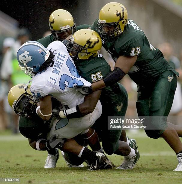 North Carolina tailback Johnny White is stopped for a loss of three yards by South Florida's Terrell McClain Jeremiah Warren and Marvin Peoples...