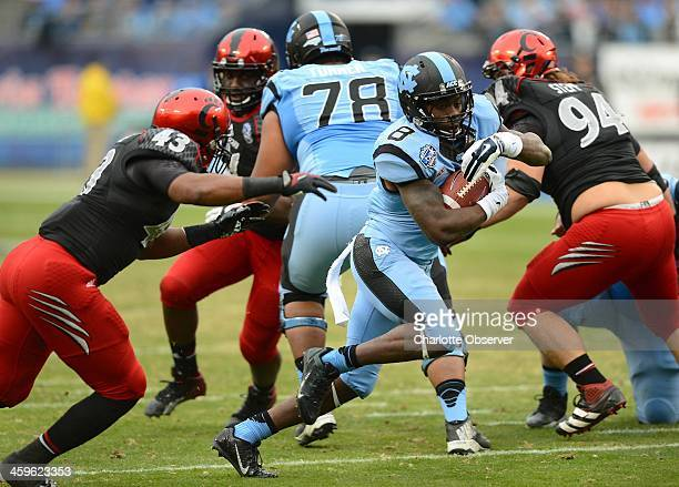 North Carolina tailback TJ Logan slices through a hole in the Cincinnati defense in the first quarter of the Belk Bowl at Bank Of America Stadium in...