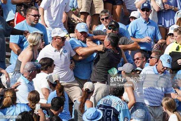 North Carolina Tar Heel and an East Carolina Pirate fan fight in the stands during a game between the East Carolina Pirates and the North Carolina...