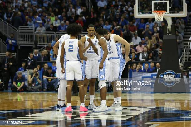 North Carolina Tar Heels forward Garrison Brooks guard Coby White and other teammates at center court to start the second half of an NCAA Midwest...