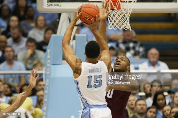 North Carolina Tar Heels forward Garrison Brooks shoots while defended by Harvard Crimson forward Chris Lewis on January 2 at the Dean Smith Center...