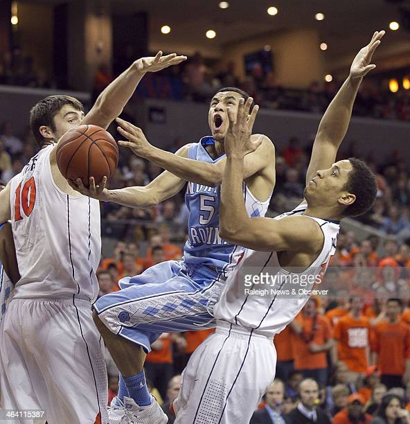 North Carolina Tar Heels' Marcus Paige finds the going tough as he goes between the Virginia Cavaliers defense of Mike Tobey and Malcolm Brogdon in...