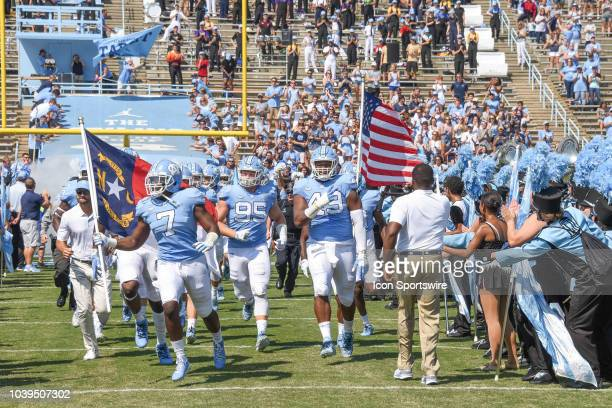 North Carolina Tar Heels wide receiver Gray Goodwyn caries the North Carolina State flag on to the field during the college football game between the...