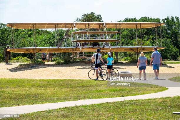 North Carolina, Wright Brothers National Memorial, couple on bicycles looking at sculpture.