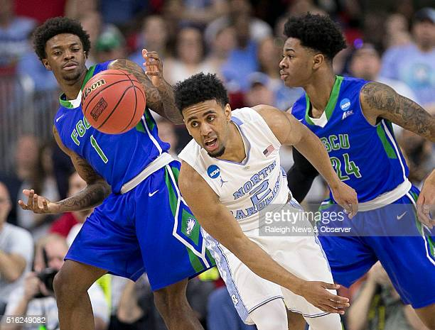 North Carolina's Joel Berry II chases a loose ball with Florida Gulf Coast's Reggie Reid and Rayjon Tucker during the first half in the first round...