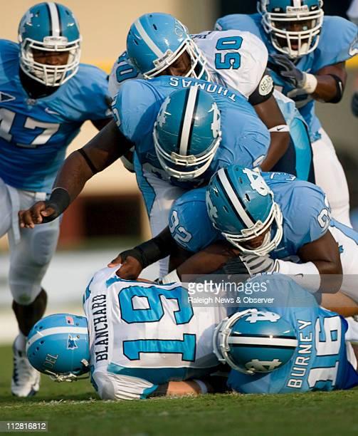 North Carolina's Kendric Burney EJ Wilson and Cam Thomas drop Citadel quarterback Bart Blanchard for a loss in the first quarter on Saturday...