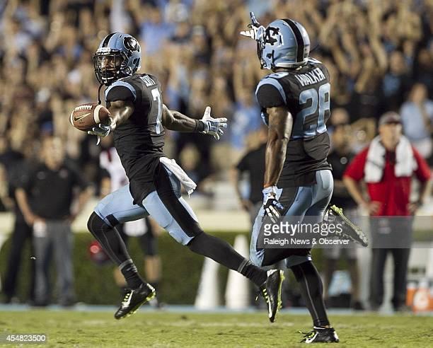 North Carolina's Tim Scott and teammate Brian Walker celebrate after Scott intercepted San Diego State quarterback Quinn Kaehler in the end zone with...