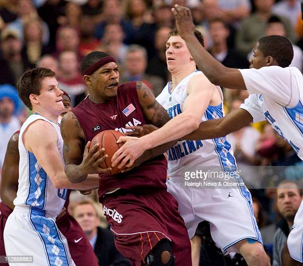 North Carolina's Tyler Hansbrough gets his hands on the ball as teammates Bobby Frasor and Ed Davis trap Virginia's Tech's JT Thompson with less than...