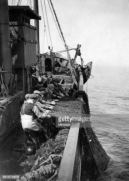 North East Coast Trawlermen heave up the nets after 5 hrs. Fishing in North Sea, and all hands go to task in hope that it will be a recond catch....