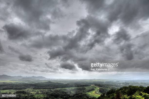 north korea landscape under a cloudy sky - military demarcation line korea stock pictures, royalty-free photos & images