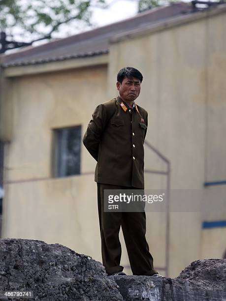 A North Korea military officer watches over the bank of the Yalu River which separates the North Korean town of Sinuiju from the Chinese border town...