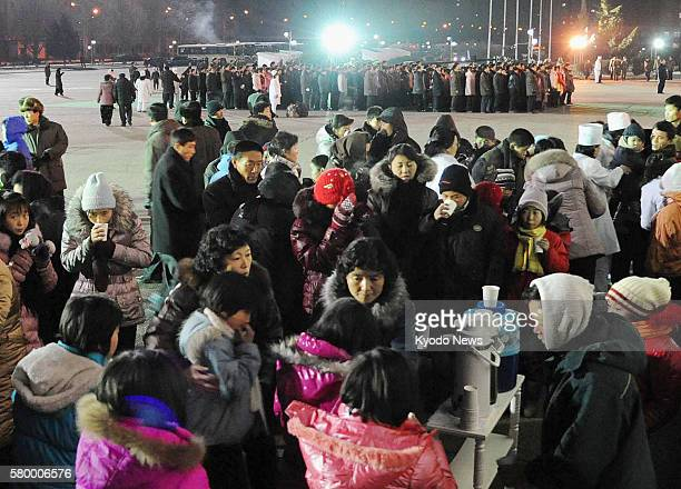 PYONGYANG North Korea North Koreans receive hot drinks handed out in the plaza in front of Pyongyang Indoor Stadium in Pyongyang as they mourn for...