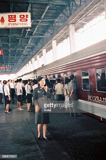 Pyongyang station agent in front of the train connecting Pyongyang with Moscow and passengers in the background Pyongyang railway station 2009