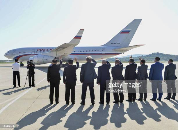 North Korean and Russian officials wave at an airplane carrying Russian Foreign Minister Sergey Lavrov at Pyongyang airport on May 31 as Lavrov...