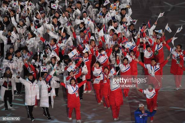 TOPSHOT North Korean and South Korean delegations wave their flags along with the Unified Korea flag during the closing ceremony of the Pyeongchang...