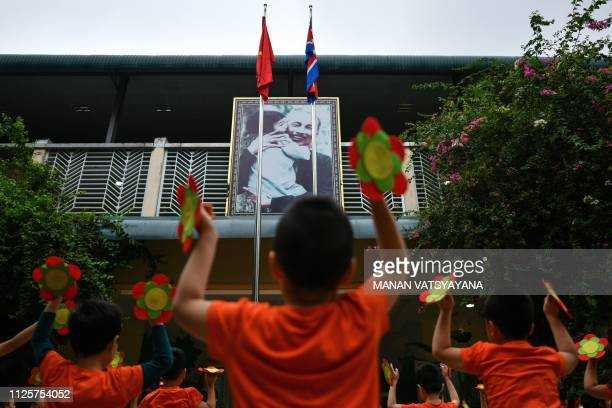 North Korean and Vietnamese flags are seen in front of a portrait of the late Vietnamese leader Ho Chi Minh as school children perform morning...