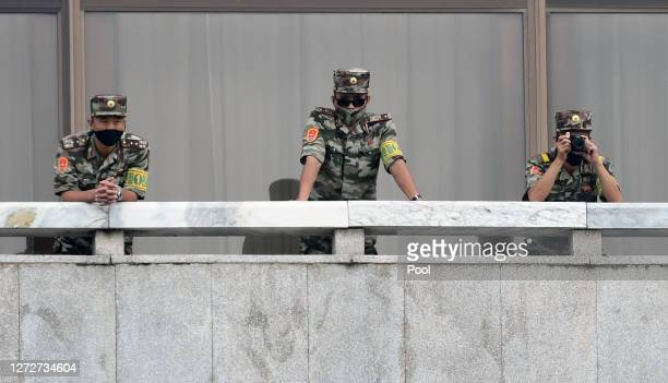 North Korean army soldiers wearing masks look at the South side during South Korean Unification Minister Lee Inyoung's visit to Panmunjom between...