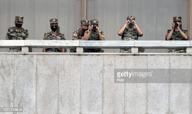 North Korean army soldiers wearing masks look at the South side during South Korean Unification Minister Lee In-young's visit to Panmunjom between...