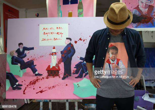 North Korean artist Sun Mu in front of a painting with Donald Trump and Kim Jong Un National Capital Area Seoul South Korea on September 7 2017 in...