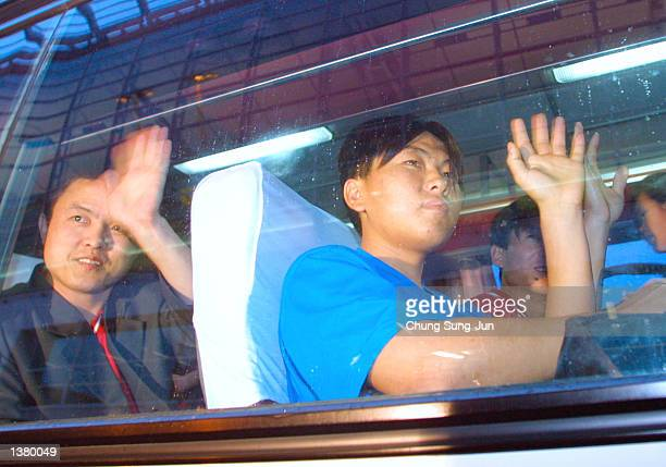 North Korean asylum seekers wave while sitting in a bus after arriving at Incheon International Airport after traveling from Beijing via the...