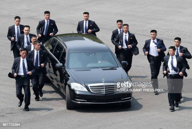 TOPSHOT North Korean bodyguards jog next to a car carrying North Korea's leader Kim Jong Un returning to the North for a lunch break after a morning...