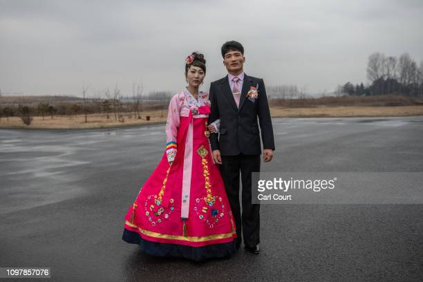 North Korean bride wearing a traditional Korean hanbok wedding dress poses for a photograph with the groom as they arrive for a wedding party at...