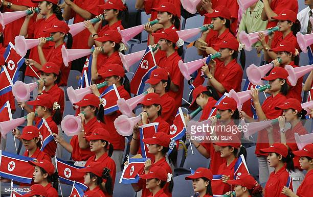 North Korean cheering squad hold their national flag and cheer 04 September 2005 The cheering squad is in Incheon to support their track and field...