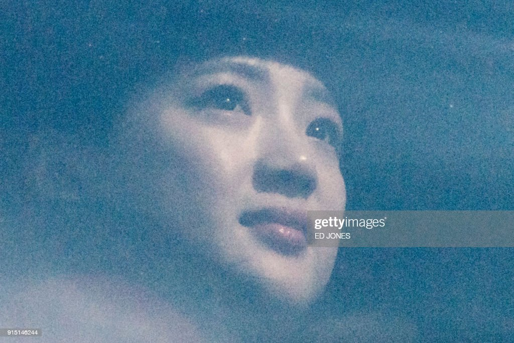 A North Korean cheerleader looks from the window of a bus convoy carrying a 280-member delegation on its way to the 2018 Pyeongchang winter Olympic games, after arriving in South Korea across the Demilitarized Zone (DMZ), on the outskirts of Seoul on February 7, 2018. More than 200 young North Korean women arrived in South Korea to root for athletes from both sides of the peninsula at the Winter Olympics. / AFP PHOTO / Ed JONES