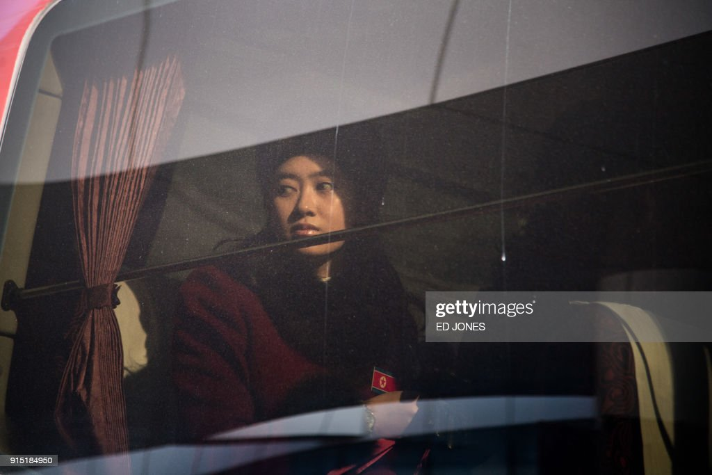 North Korean cheerleader sits aboard a bus as their convoy arrives at the Inje Speedium resort complex, where they are staying during the Pyeongchang 2018 Winter Olympic Games on February 7, 2018. More than 200 young North Korean women arrived in South Korea to root for athletes from both sides of the peninsula at the Winter Olympics. / AFP PHOTO / Ed JONES