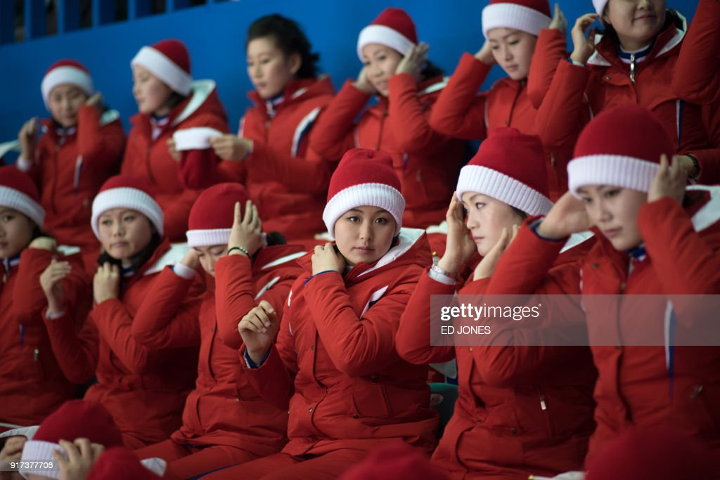 North Korean cheerleaders attend the women's preliminary round ice hockey match between Sweden and Unified Korea during the Pyeongchang 2018 Winter Olympic Games at the Kwandong Hockey Centre in Gangneung on February 12, 2018. / AFP PHOTO / Ed JONES