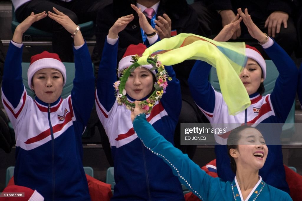 TOPSHOT - North Korean cheerleaders attend the women's preliminary round ice hockey match between Sweden and Unified Korea during the Pyeongchang 2018 Winter Olympic Games at the Kwandong Hockey Centre in Gangneung on February 12, 2018. / AFP PHOTO / Ed JONES
