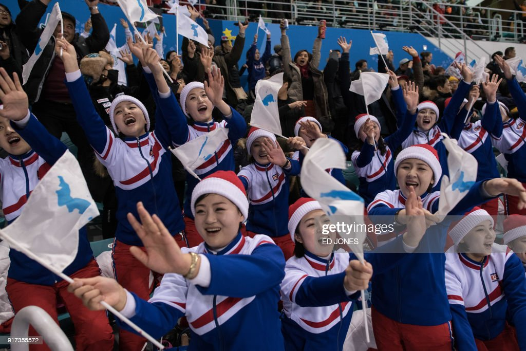 TOPSHOT - North Korean cheerleaders hold the flags of the unified Korean team during the women's preliminary round ice hockey match between Korea and Sweden, at the Ice Arena in Gangneung on February 12, 2018. / AFP PHOTO / Ed JONES