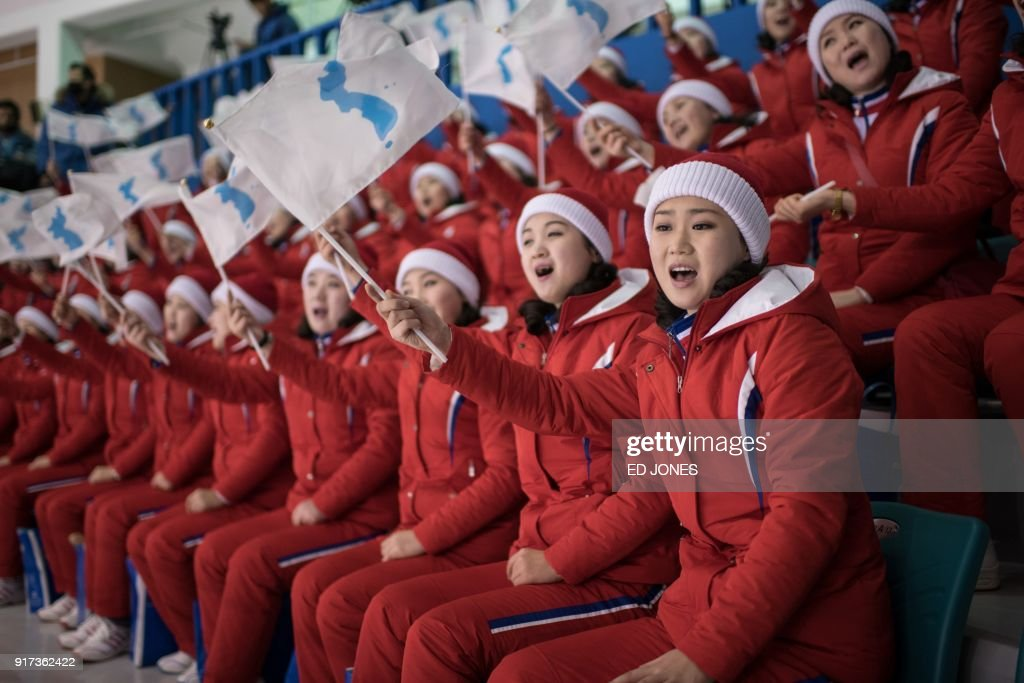 TOPSHOT - North Korean cheerleaders hold the flags of the unified Korean team during the womens preliminary round ice hockey match between Korea and Sweden, at the Ice Arena in Gangneung on February 12, 2018. / AFP PHOTO / Ed JONES