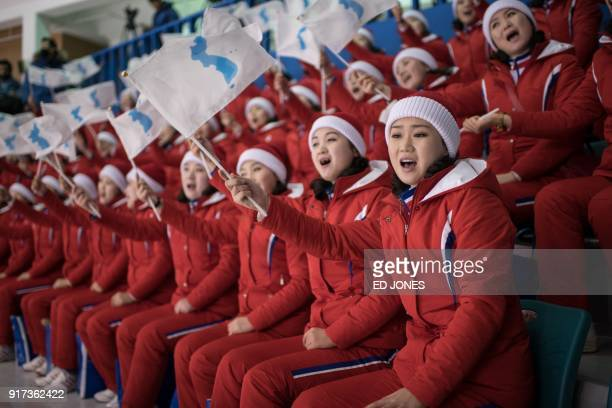 TOPSHOT North Korean cheerleaders hold the flags of the unified Korean team during the womens preliminary round ice hockey match between Korea and...