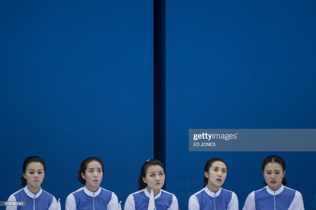 North Korean cheerleaders react as they attend the Unified Korean ice hockey team play against Japan during the Pyeongchang 2018 Winter Olympic Games at the Kwandong Hockey Centre in Gangneung on February 14, 2018. / AFP PHOTO / Ed JONES