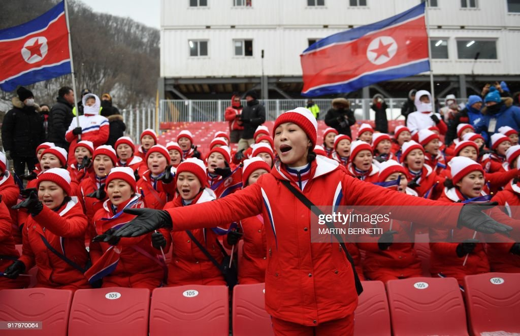 TOPSHOT - North Korean cheerleaders sing as the Alpine Skiing Women's Slalom was cancelled due to weather conditions at the Jeongseon Alpine Center during the Pyeongchang 2018 Winter Olympic Games in Pyeongchang on February 14, 2018. / AFP PHOTO / Martin BERNETTI