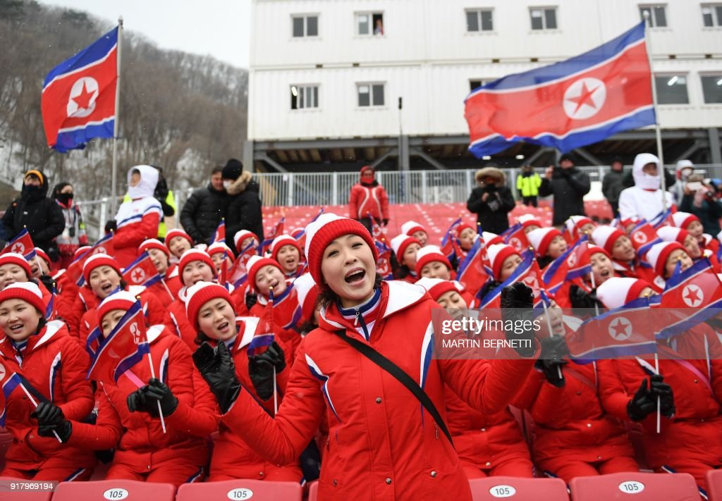 North Korean cheerleaders sing as the start of the Alpine Skiing Women's Slalom was delayed due to weather conditions at the Jeongseon Alpine Center during the Pyeongchang 2018 Winter Olympic Games in Pyeongchang on February 14, 2018. / AFP PHOTO / Martin BERNETTI
