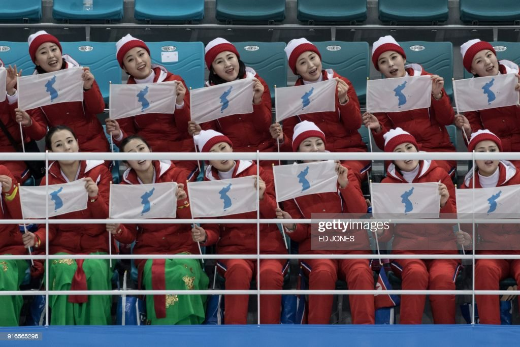North Korean cheerleaders wave flags showing a unified Korean peninsula as they perform following the women's preliminary round ice hockey match between the unified Korea team and Switzerland at the Pyeongchang 2018 Winter Olympics, at the Gangneung Ice Arena in Gangneung on February 10, 2018. / AFP PHOTO / Ed JONES