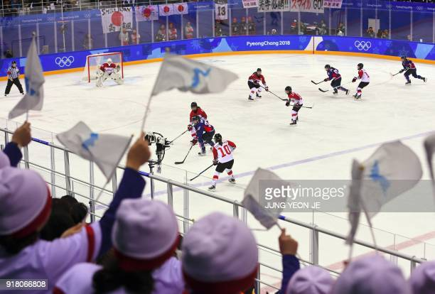 North Korean cheerleaders wave the Korean unification flags and cheer during the women's preliminary round ice hockey match between Japan and the...