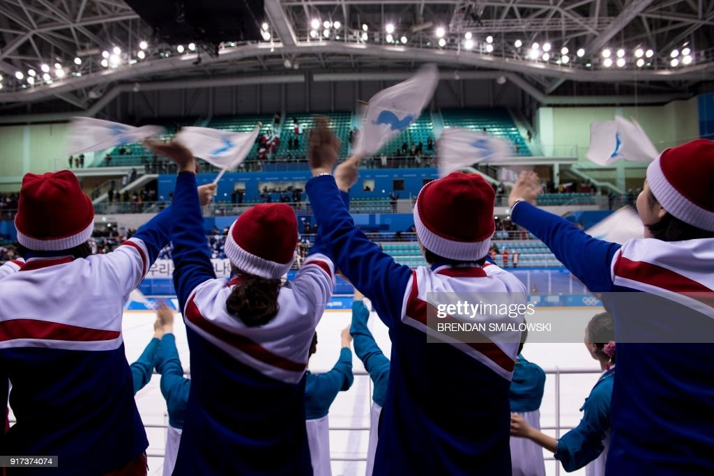 TOPSHOT - North Korean cheerleaders wave the Unified Korea flags after the women's preliminary round ice hockey match between Sweden and Unified Korea during the Pyeongchang 2018 Winter Olympic Games at the Kwandong Hockey Centre in Gangneung on February 12, 2018. / AFP PHOTO / Brendan Smialowski