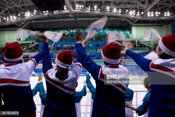 TOPSHOT North Korean cheerleaders wave the Unified Korea flags after the women's preliminary round ice hockey match between Sweden and Unified Korea...