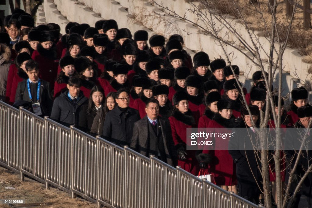 North Korean cheerleads walk between a hotel and a condominium at the Inje Speedium resort complex, where they are staying during the 2018 Pyeongchang winter Olympic games, on February 7, 2018. More than 200 young North Korean women arrived in South Korea to root for athletes from both sides of the peninsula at the Winter Olympics. / AFP PHOTO / Ed JONES